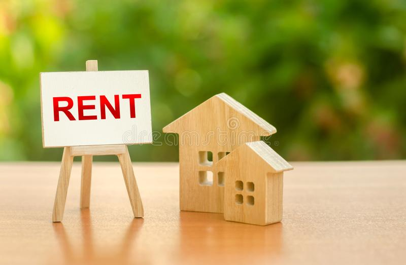 Two figures of houses and an easel with the word rent. The concept of temporary rental housing and real estate. Realtor services. Search for optimal options royalty free stock images