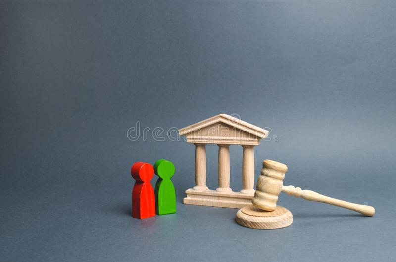 Two figures of people opponents stand near the courthouse and the judge`s gavel. Conflict resolution in court, claimant royalty free stock photo