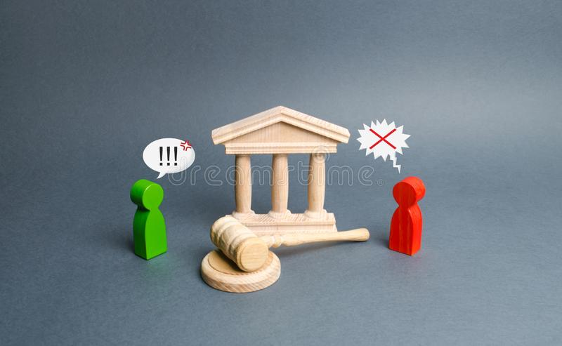 Two figures of people opponents stand near the courthouse and the judge`s gavel. Conflict resolution in court, claimant stock photo