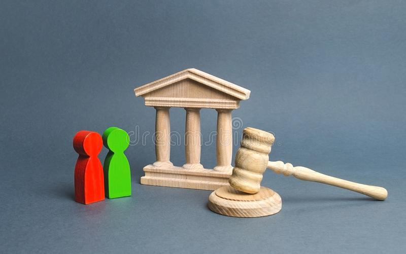 Two figures of people opponents stand near the courthouse and the judge`s gavel. Conflict resolution in court, claimant. And respondent. Court case, settling royalty free stock image