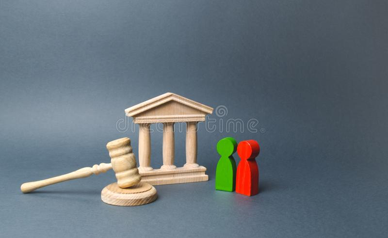Two figures of people opponents stand near the courthouse and the judge`s gavel. The judicial system. Conflict resolution stock images