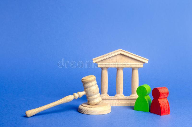 Two figures of people opponents stand near the courthouse and the judge`s gavel. The judicial system. Conflict resolution. In court, claimant and respondent stock image