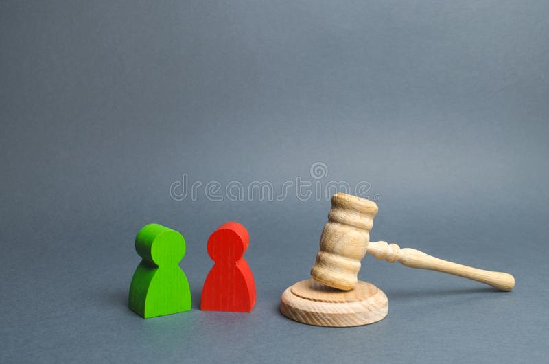 Two figures of people opponents stand near the judge`s gavel. Conflict resolution in court, claimant and respondent. Court case stock image