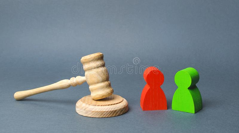 Two figures of people opponents stand near the judge`s gavel. The judicial system. Conflict resolution in court, claimant. And respondent. Court case royalty free stock photography