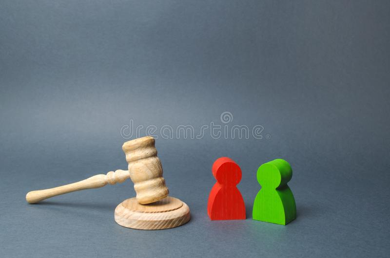 Two figures of people opponents stand near the judge`s gavel. The judicial system. Conflict resolution in court, claimant royalty free stock photo