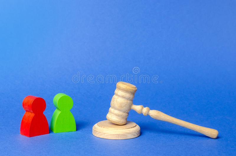 Two figures of people opponents stand near the judge`s gavel. The judicial system. Court case, settling disputes. Legal advice stock photography