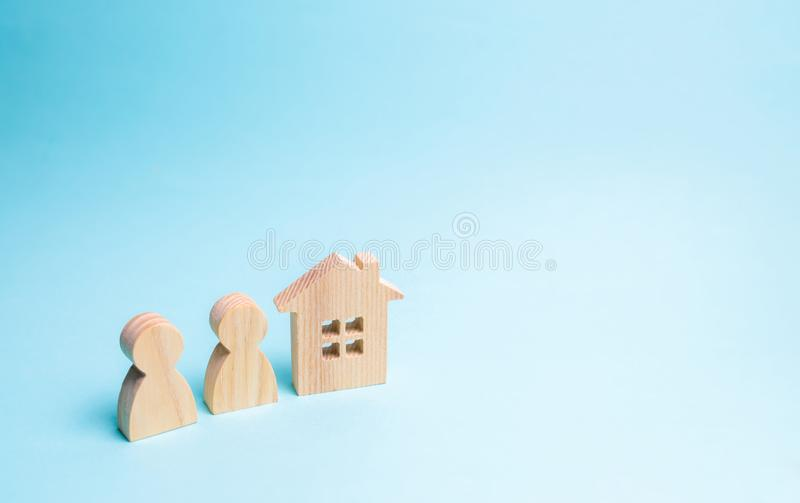 Two figures of people and a wooden house on a blue background. The concept of affordable housing and mortgages for buying a home royalty free stock photography
