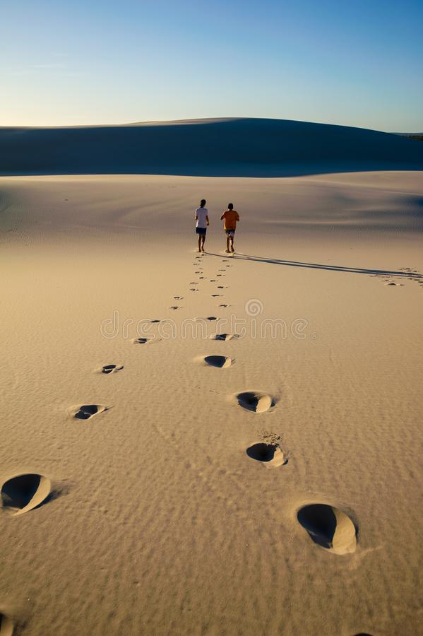 Tracks left by two figures walking into the distance across a deserted sand dune royalty free stock images