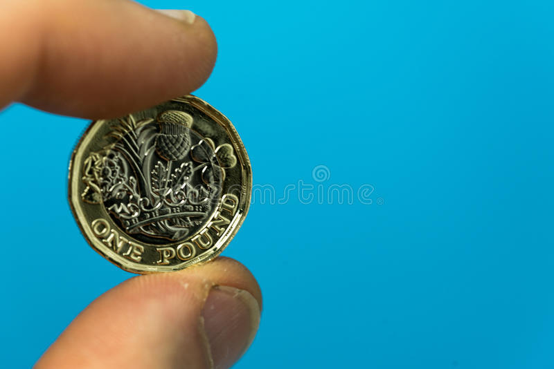 Two fingers holding the new UK pound coin on a blue background. Two fingers holding the new pound coin introduced in the UK in 2017, front, on a blue background royalty free stock photos