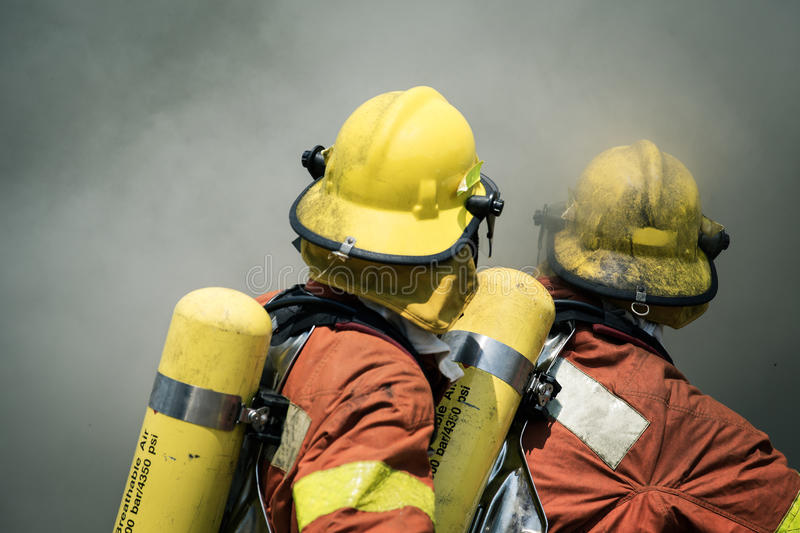 Two firefighters fire fighting suround with dark smoke royalty free stock photos