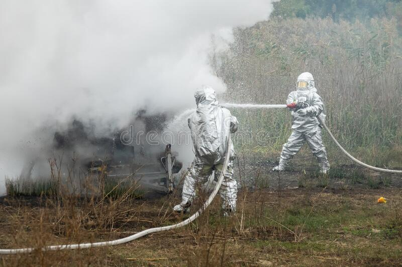 Two firefighters in protective suits works with water hose. Fighting for a fire attack. Firefighters in protective suits works with water hose. Fighting for a royalty free stock image