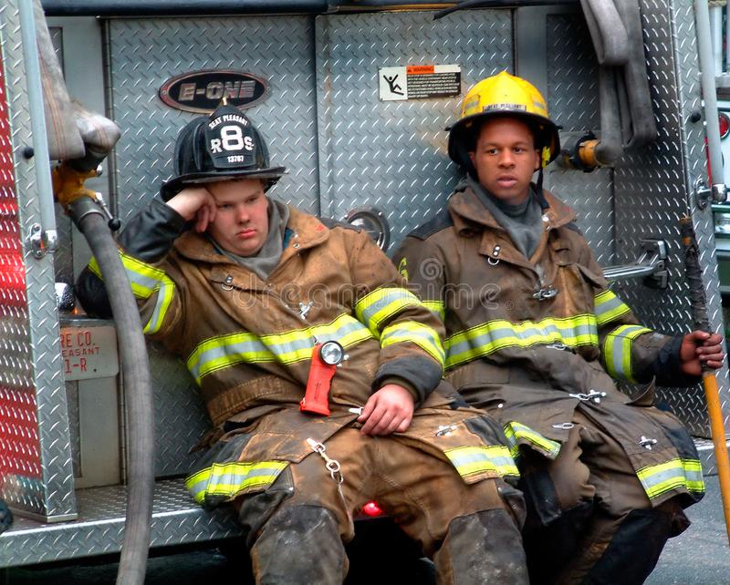 Two firefighters taking a break ifrom fire fighting at a house fire t stock photo