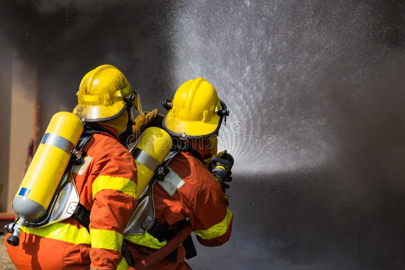 Two firefighters water spray by high pressure nozzle surround wi stock images
