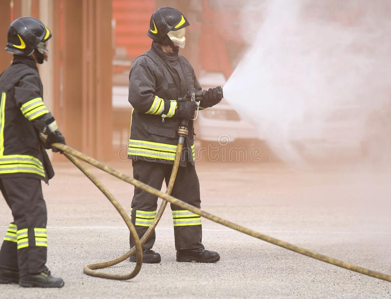 Two firemen with a mask shut down a fire. Two firemen with the mask extinguish a fire with white foam royalty free stock photography