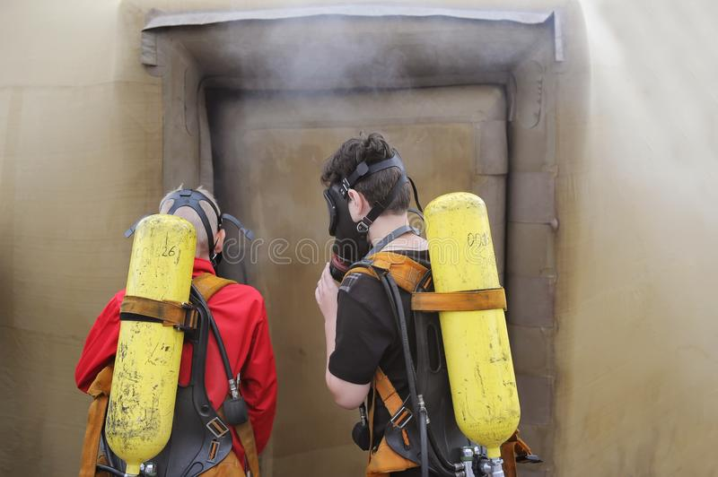 Two firemen with oxygen cylinders in protective suits in protective masks. Go to a smoke house royalty free stock images