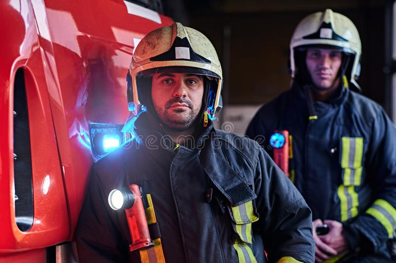 Two firemen wearing protective uniform standing next to a fire truck in a garage of a fire department. royalty free stock photo