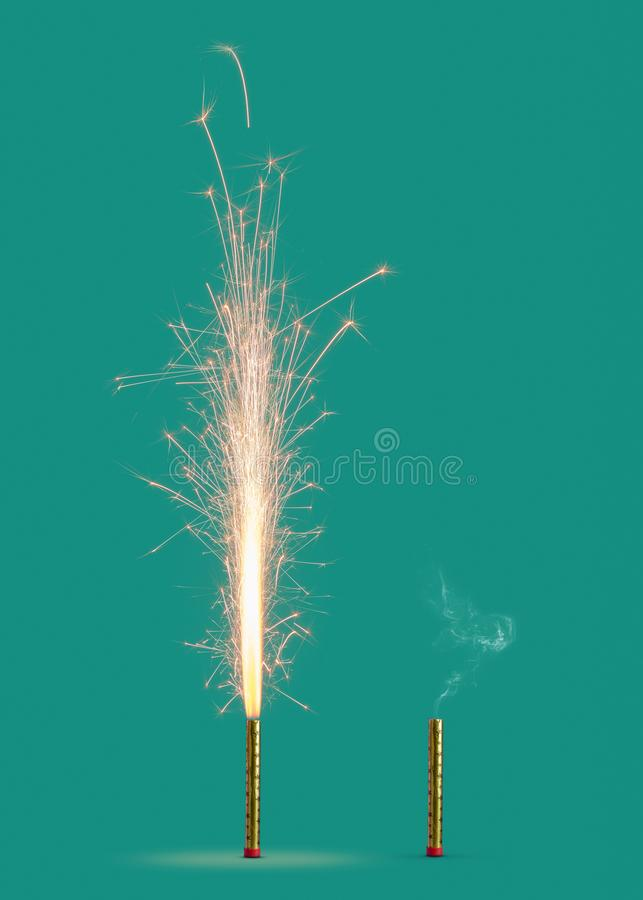 Two fireworks burning and burnt on a turquoise background. Burning firework with bright sparkes and smoke from burnt candle on a turquoise background, copy royalty free stock photography