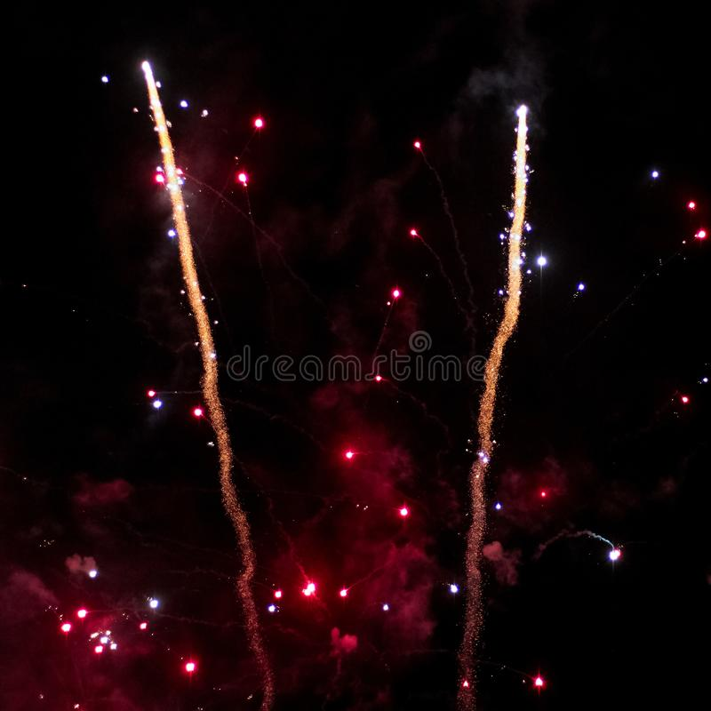 Two Fireworks rockets ascend into the sky. With deep red smoke stock image