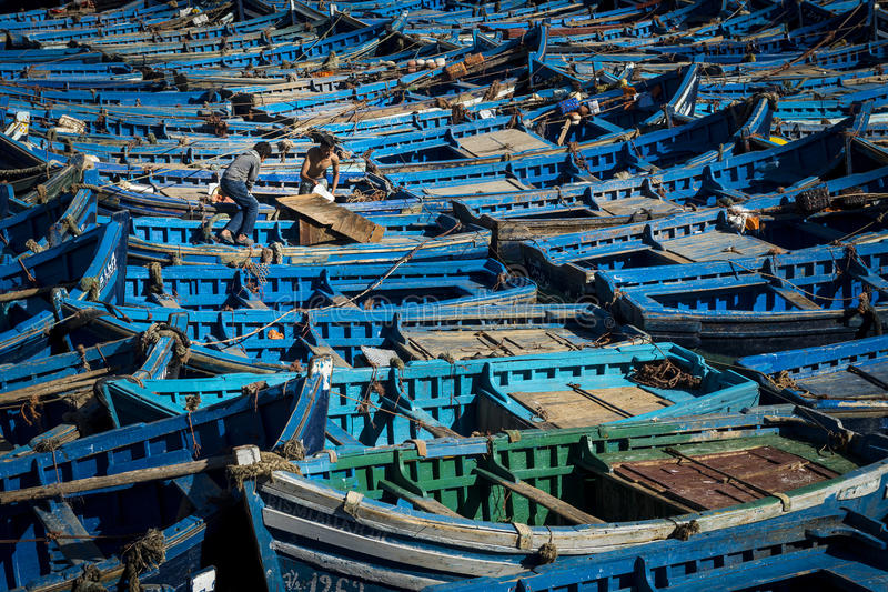 Two fisherman working in the traditional blue fishing boats docked in the fishing harbour of Essouria in the Atlantic Coast of Mor stock photos