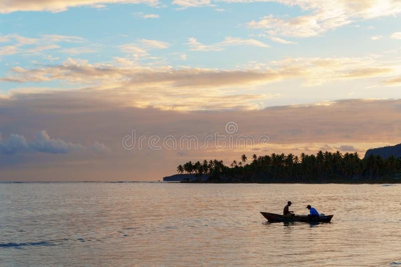 Two fishermen in a boat going fishing early in the morning at dawn royalty free stock photography