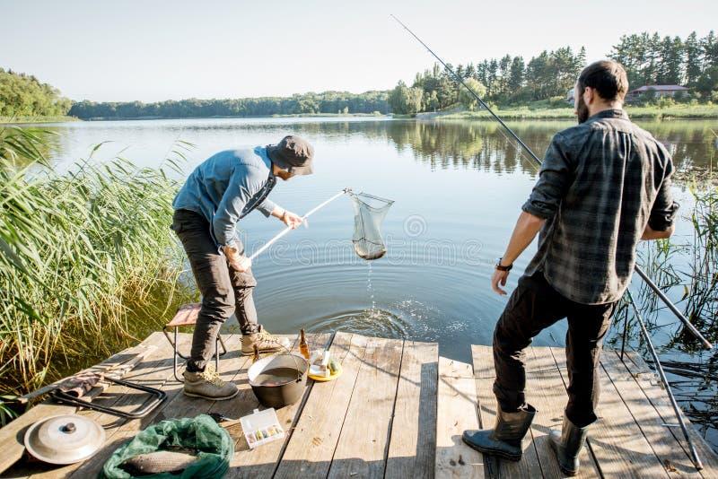 Fishermen catching fish with net. Two fishermen catching fish with fishing net on the lake in the morning stock image