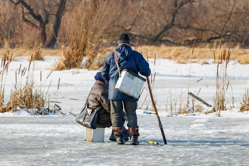 Two fishermen on the ice of the lake. Ice winter fishing royalty free stock images