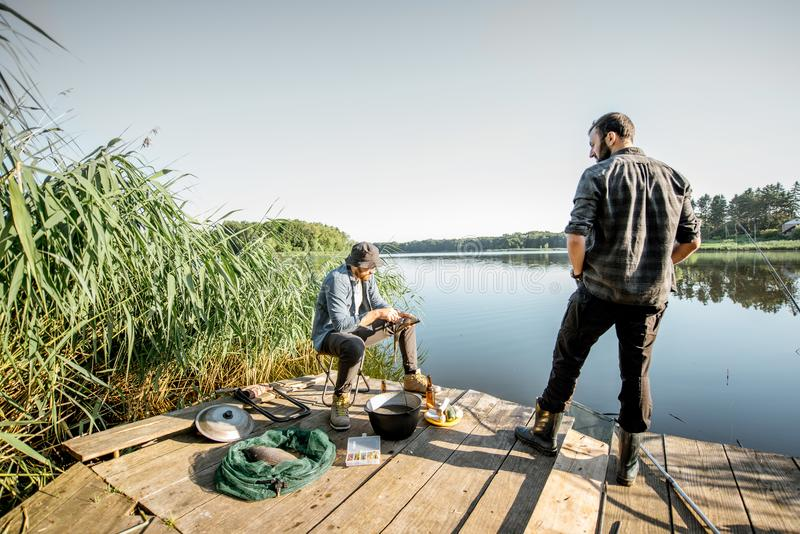 Fishermen on the picnic near the lake. Two fishermen relaxing during the picnic on the wooden pier near the lake in the morning stock photo
