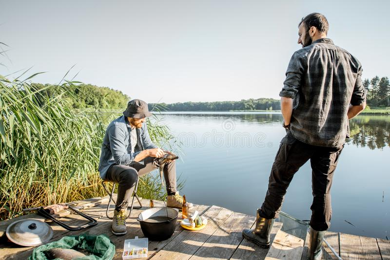 Fishermen on the picnic near the lake. Two fishermen relaxing during the picnic on the wooden pier near the lake in the morning stock images
