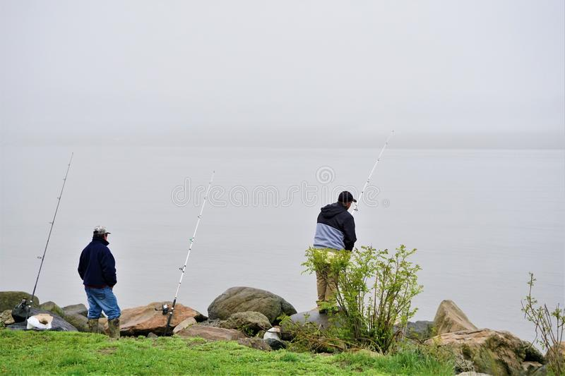Two fishermen with three poles along Hudson river. Two men fish the estuary for dinner by propping poles amidst the rocks and await a bite. Subsistence fishing stock photo