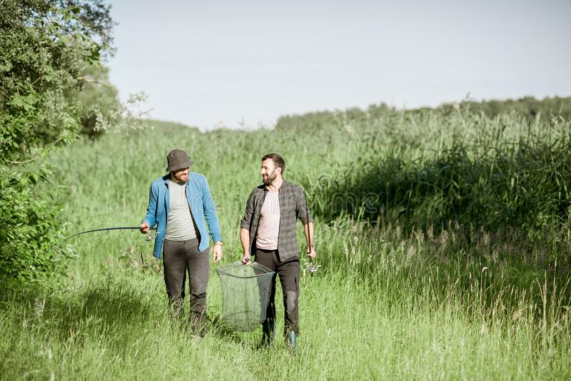 Fishermen walking on the green lawn. Two fishermen walking with fishing rod and net on the green lawn near the lake in the morning stock photography