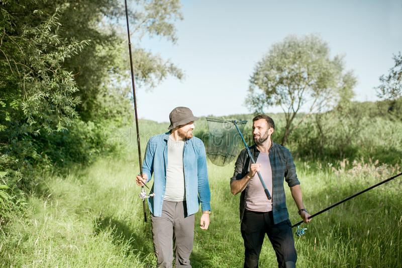 Fishermen walking on the green lawn. Two fishermen walking with fishing rod and net on the green lawn near the lake in the morning stock photos
