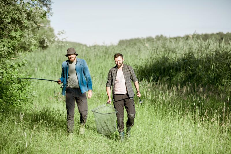 Fishermen walking on the green lawn. Two fishermen walking with fishing rod and net on the green lawn near the lake in the morning royalty free stock image