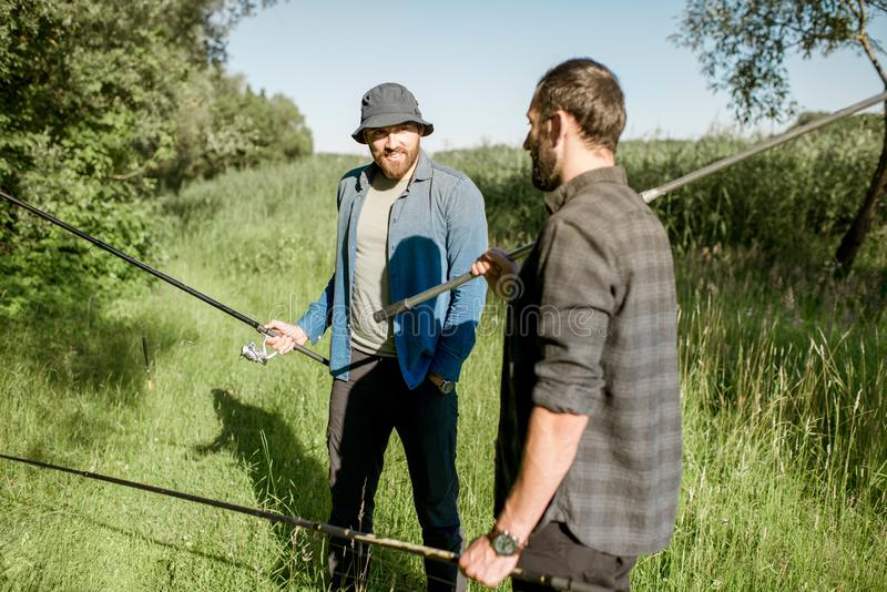 Fishermen walking on the green lawn. Two fishermen walking with fishing rod and net on the green lawn near the lake in the morning stock image