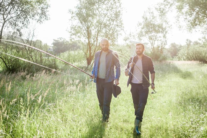 Fishermen walking on the green lawn. Two fishermen walking with fishing rod and net on the green lawn near the lake in the morning royalty free stock photo