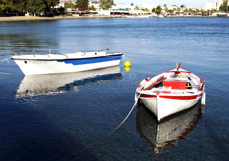Two fishing boats with water reflections. Greece royalty free stock images
