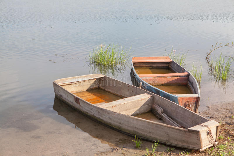 Two fishing boats. Two fishing wooden boats on the river water royalty free stock photo