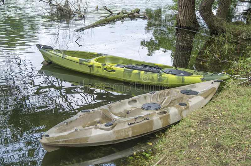 Two fishing single seat kayak on the river. In cloudy day stock photos