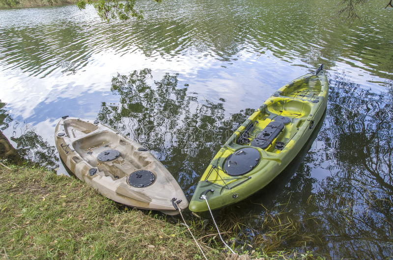 Two fishing single seat kayak on the river. In cloudy day stock image