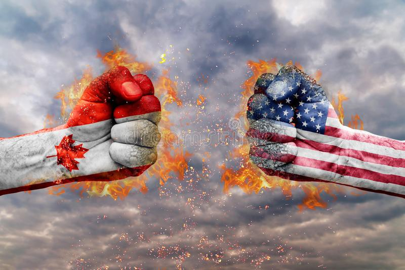 Two fist with the flag of Canada and USA faced at each other. Ready for fight stock photography