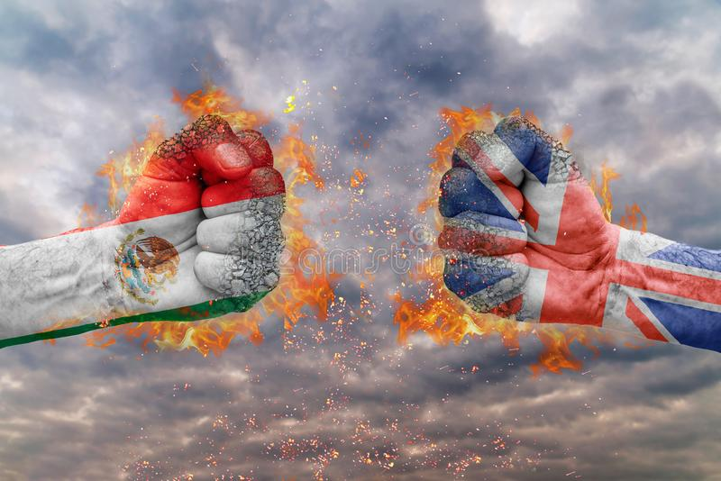 Two fist with the flag of Mexico and Great Britain faced at each other. Ready for fight stock image