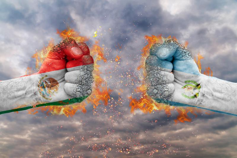 Two fist with the flag of Mexico and Guatemala faced at each other. Ready for fight royalty free stock image