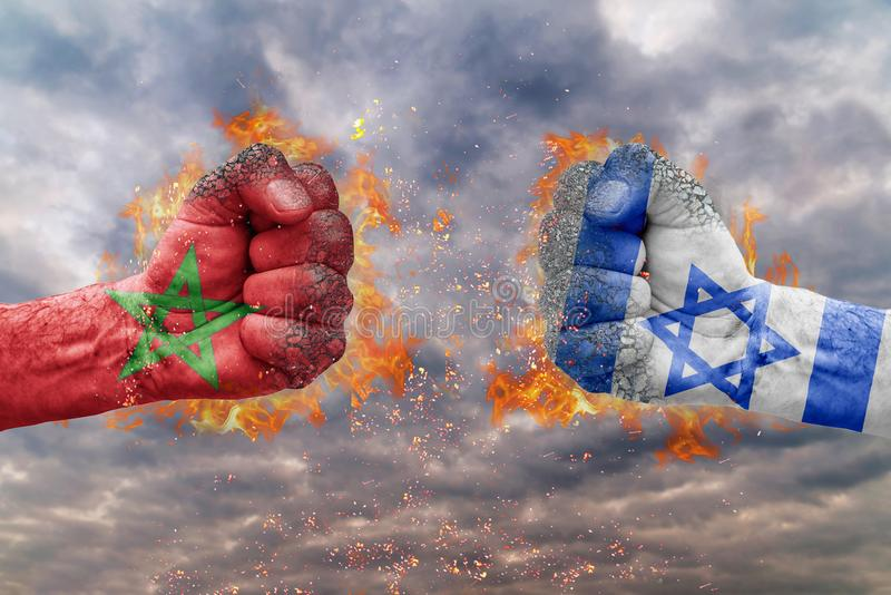 Two fist with the flag of Morocco and Israel faced at each other royalty free stock image