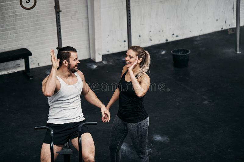 Fit people high fiving together after a stationary bike workout royalty free stock photos