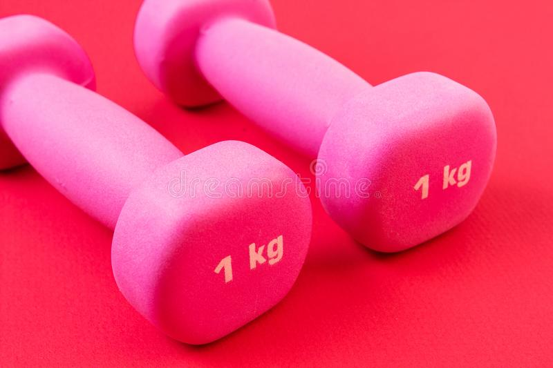 Two fitness dumbbells on pink royalty free stock photo