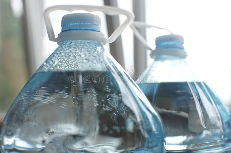 Two five-liter plastic bottles full of water, close-up of the top with lids and handles royalty free stock image