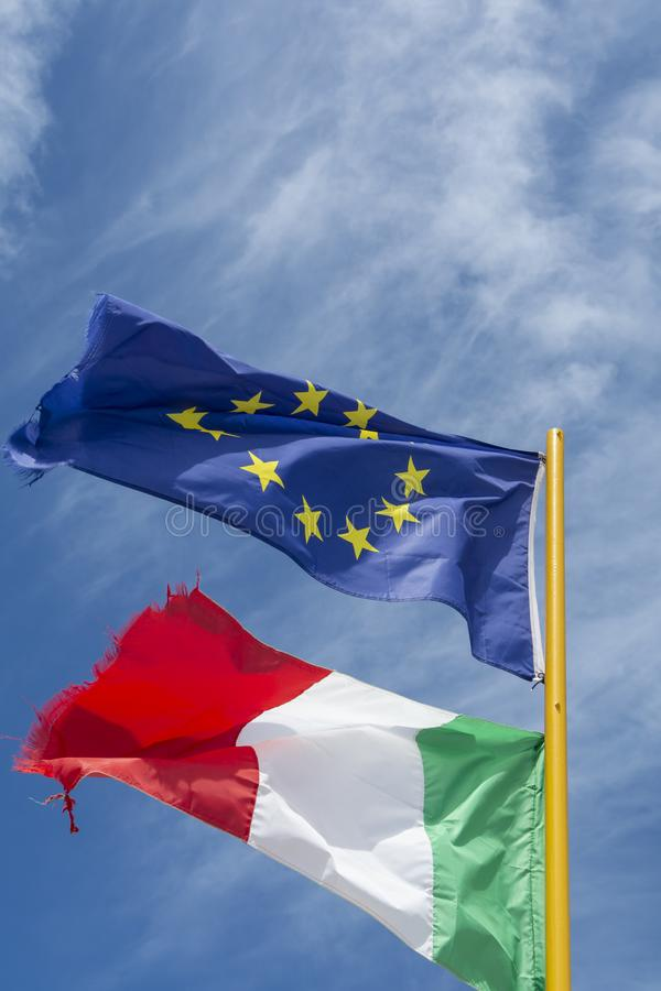 Two flags of Italy and European Union  fluttering in the wind stock photography