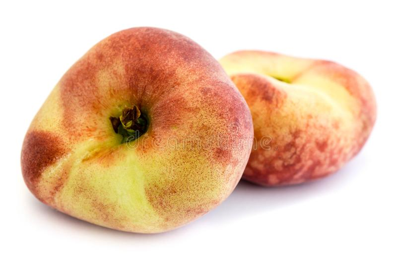 Two flat peaches isolated on white background stock images