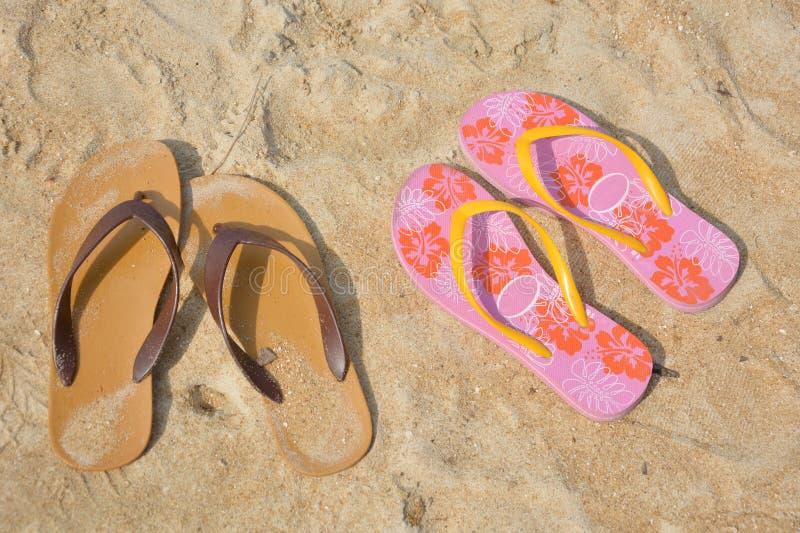 Two flip flops on a sandy ocean beach. Two flip flops brown and pink colour on a sandy ocean beach stock image