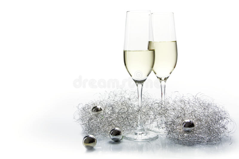 Two flutes champagne glasses for new year and silver decoration. Two Flutes champagne glasses and silver decoration on a white background, concept for new years royalty free stock photo