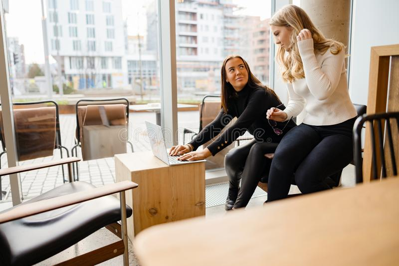 Two Focused Women Working Togehter On Laptop At Cafe In City royalty free stock images